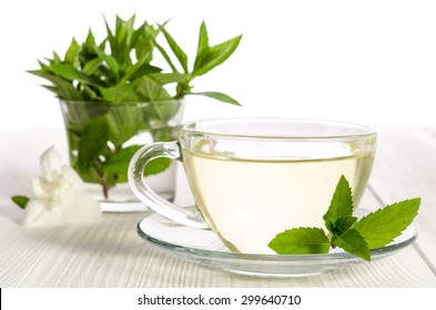 Glass cup of tea with jasmine and mint on the white background