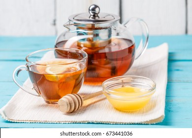 Glass cup of tea with lemon, glass teapot and honey on blue wooden table.