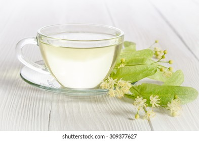 Glass cup of tea with linden on white  wooden table