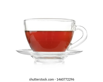 Glass cup of tea and saucer on white background