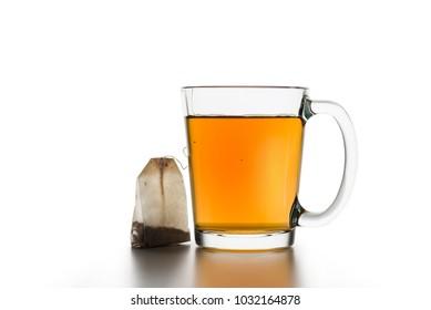 glass cup of tea with tea-bag on white table