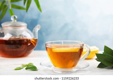 Glass cup and teapot with black tea on wooden table