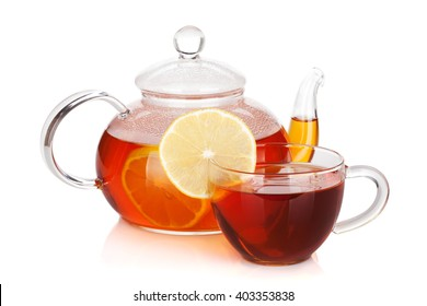 Glass cup and teapot of black tea with lemon. Isolated on white background