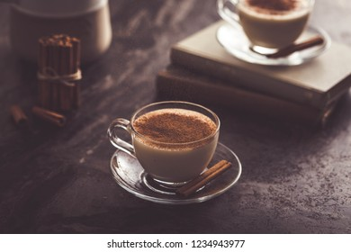 Glass cup of Turkish salep (milky traditional hot drink) with cinnamon sticks on dark wood