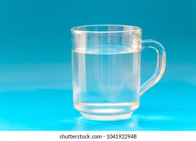 Glass cup with water on blue background. Selective focus wtih shallow depth of field.