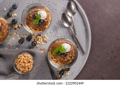 Glass cups of chocolate and chestnuts mousse with roasted almonds and oats decorated with black berries and mint leaves.