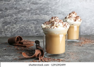Glass cups of tasty coffee with whipped cream on gray table