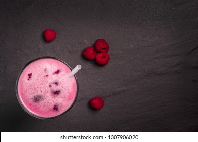 A glass of dairy free milkshake with fresh organic raspberries on a dark stone background with copy space
