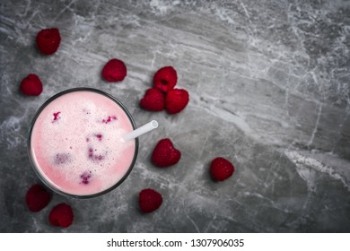 A glass of dairy free milkshake with fresh organic raspberries on a marble stone background with copy space