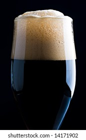 Glass of dark beer with beautiful foam close up