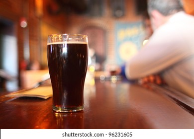 Glass of dark beer on the counter at a bar. (Soft Focus. Shallow DOF)