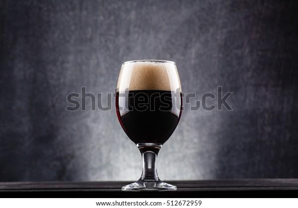 Glass of dark beer over a dark textured wooden background
