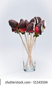 Glass of dark chocolate coated strawberries on the sticks