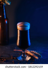 A glass of dark craft  beer porter or stout on the table. Trendy colored light