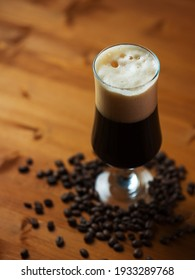 A glass of dark craft beer porter or stout, roasted coffee beans. Craft beer with coffee