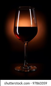 Glass of dark red wine on the black background