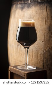 Glass of dark stout beer standing near an old wooden barrel in a cellar
