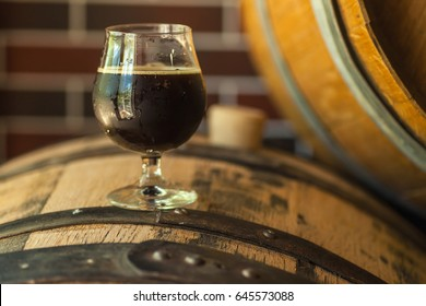 Glass of dark stout beer standing on an oak wood barrel in a brewery