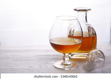 Glass and glass decanter with alcohol. Cognac Decanter. Carafe of brandy.
