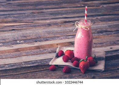 Glass of delicious berry smoothie on wooden background. Side view.