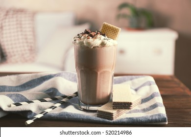 Glass of delicious chocolate milkshake with napkin on wooden table