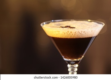 Glass of delicious Espresso Martini on blurred background. Alcohol cocktail