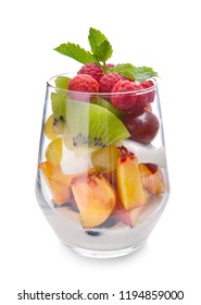 Glass with delicious fruit salad, cream and mint on white background