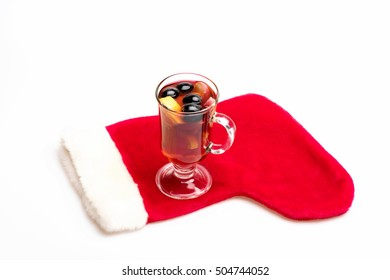 Glass of delicious glintwein or mulled hot wine with Santa Claus red sock isolated on white background
