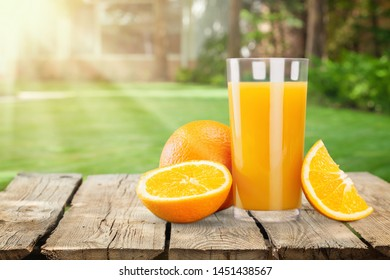 Glass of delicious orange juice on natural background