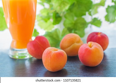 Glass of delicious peach juice and peaches on table