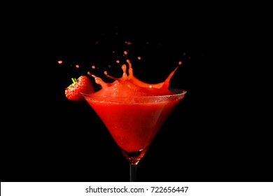 Glass of delicious strawberry daiquiri with splash on black background