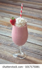 Glass of delicious strawberry smoothie on wooden background. Side view.