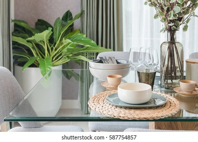 glass dining table with table set in modern dining room interior design concept
