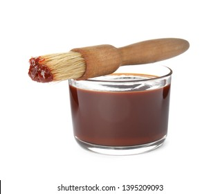 Glass dish of barbecue sauce with basting brush on white background