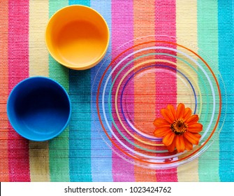 Glass dish with colorful design on a placemat with two plastic cups and a zinnia