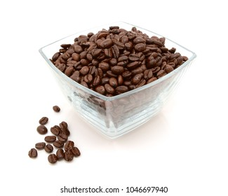 Glass dish filled with roasted coffee beans with some spilled beside on a white background