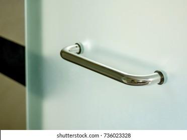 Glass door handle of a glass partition shower unit. Bathroom glass door detail opening into wet area,selective focus.
