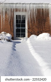 Glass door in a red brick wall nearly occluded by long sharp icicles.  Path to the doorway is covered in snow.