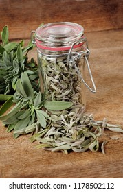 glass with dried sage and fresh sage over wooden background