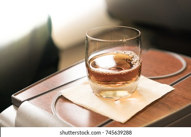 A glass of drink at business class cabin seat of an aircraft.