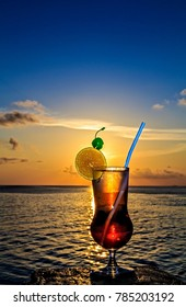 Glass of drink is on a beach table (Maldives, The Indian Ocean)
