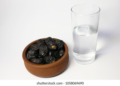 Glass of drinking water and dates. Ramadan breakfast of dates and water. Sweet and nutritious date fruits and glass of pure drinking water. Ramadan