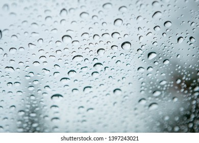 Glass with drops of rain water close up