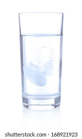 Glass with efervescent tablet in water with bubbles isolated on white