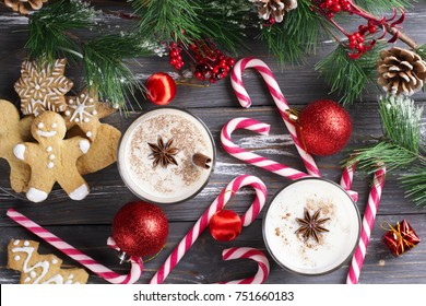 Glass of eggnog with gingerbread on wooden background