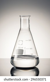 A glass Erlenmeyer flask with water(liquid, fluid) on the reflected desk in the laboratory