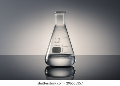 A glass Erlenmeyer flask with water(liquid, fluid) on the reflected black desk in the laboratory