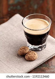 Glass of Espresso with Biscotti. Brown wooden background. Close up.