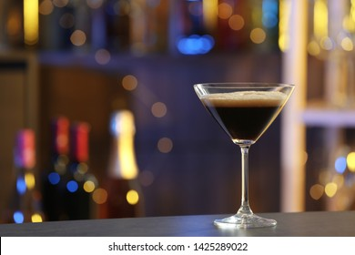 Glass of Espresso Martini on counter in bar, space for text. Alcohol cocktail
