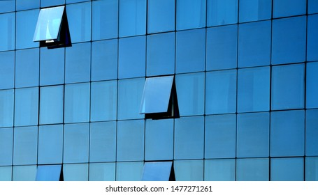 glass facade of modern business building with partly opened windows reflecting blue sky